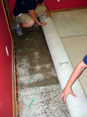 Ridgecrest water damaged carpet being removed by two men.